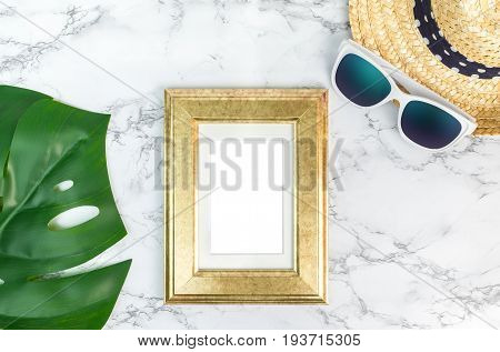 Blank Vintage Golden Color Picture Frame On Green Monstera Leaf With Sunglasses And Straw Hat On Whi