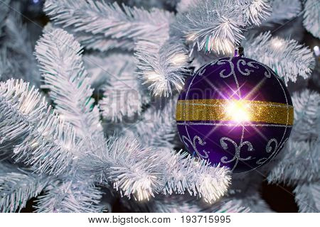 Background for cards for Christmas. Glass blue ball, toy, Christmas lights, Christmas decorations on blue paper a spruce branch.