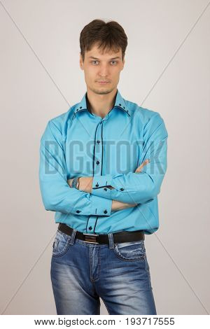 Sexy stylish young guy in jeans a blue shirt and a black jacket