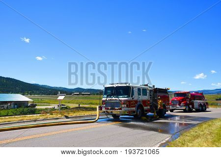KALISPELL, MONTANA, USA - June 21, 2017: Firefighter working the hose on a fire truck at grass fire scene