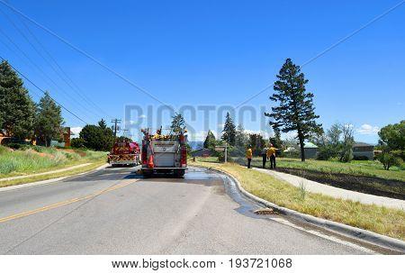 KALISPELL, MONTANA, USA - June 21, 2017: Fire crew observe grass fire scene as a water truck leaves the scene