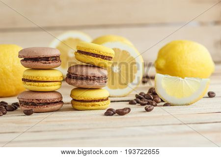 Yellow And Brown French Macarons With Lemons And Coffee Beans On The Wooden Board