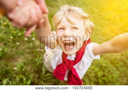 Happy smiley boy in summer playing romp with father and having fun