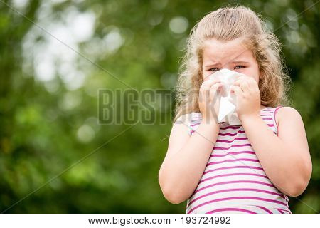 Ill child with a cold or flu sneezes and cleans nose with tissue