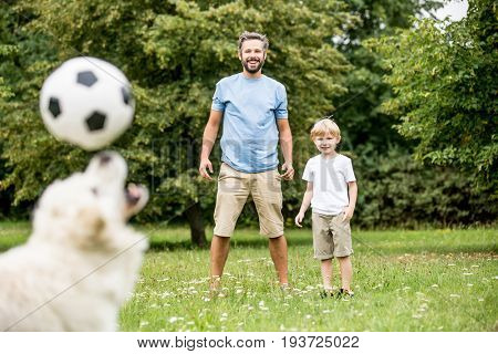 Dog juggles football with nose while playing with his family
