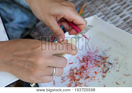 Female hands with a knife sharpened colored pencils