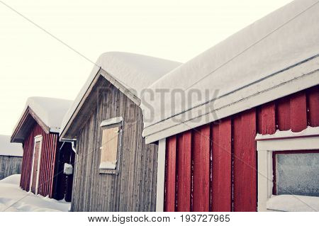 Three small houses/cabins standing close together in winter with lots of snow on the roof tops.