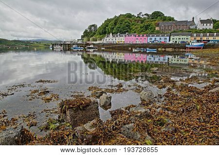 View of Portree harbor with reflections and colorful houses, seen from the seashore, Isle of Skye, Highlands, Scotland, UK