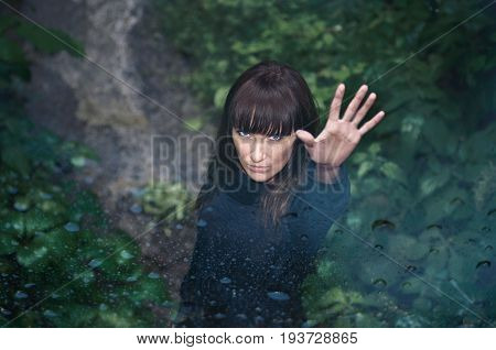 Attractive mysterious young woman with raised left hand in a beautiful rainy park