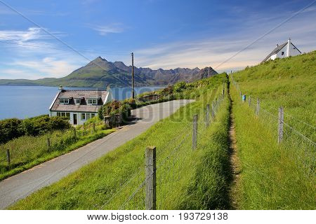 ISLE OF SKYE, UK - JUNE 20, 2017: View of the Black Cuillin mountain range across Loch Scavaig from the coastal path near Elgol with traditional houses in the foreground