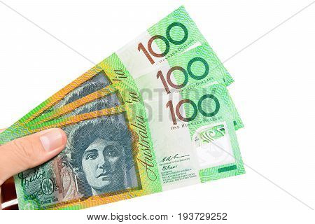 Hand holding money Australian dollar (AUD) banknotes isolated on white background