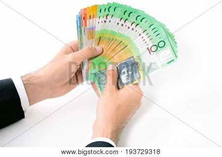 Businessman hands holding money Australian dollar (AUD) banknotes on white background