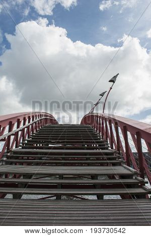 Wooden stairway in the blue sky with clouds