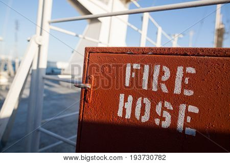 Color image of a red fire hose on a ship.