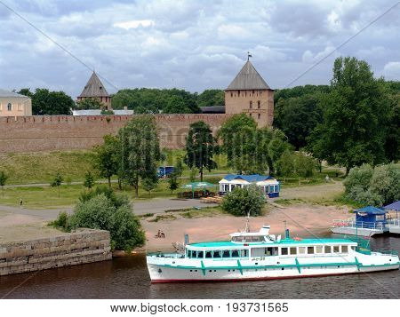 VELIKIY NOVGOROD, RUSSIA - JUNE 2007: Tourist boat approaching dock at ancient walls of Kremlin on Volkhov River on overcast cloudy summer day