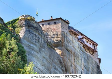 Meteora monastery on the high rock and road in the mountains at spring time, Greece