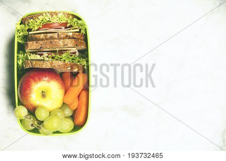 Green school lunch box with sandwich, apple, grape and carrot close up on white background. Healthy eating habits concept. Flat lay composition (from above, top view).