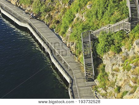 Beautiful summer season specific photograph. Pier/walkway/harbor/wooden path close to the ocean. Photo taken from above. Green vegetation, plants and rocks next to the wooden walkway.