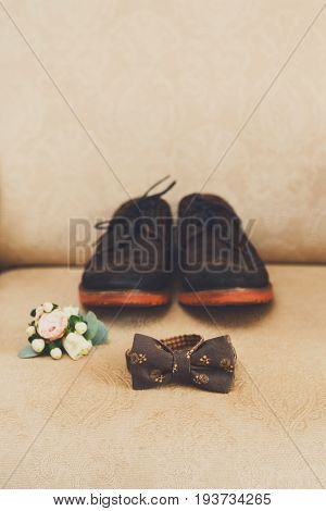 Wedding accessories, morning of groom, clothing details. Close-up of brown bow-tie, shoes and boutonniere for bridegroom, nobody, objects, indoors