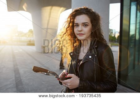 People urban lifestyle leisure modern technology and communication concept. Fashionable young female with long curly hair typing text message on electronic device posing outdoors with her bicycle