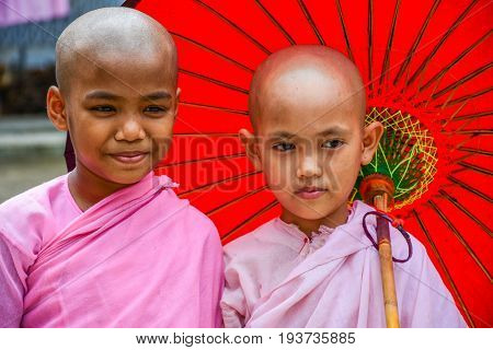 DAWEI MYANMAR - JULY 11 2015: Nuns in pink robes with red paper umbrella in Buddhist temple in Dawei of Myanmar.