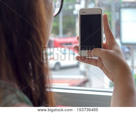 Hand holding smartphone white screen orange sunshine. smartphone vintage tone. smartphone black coler. woman using smartphone. using smartphone in coffee shop. using smartphone white screen. girl using smartphone.