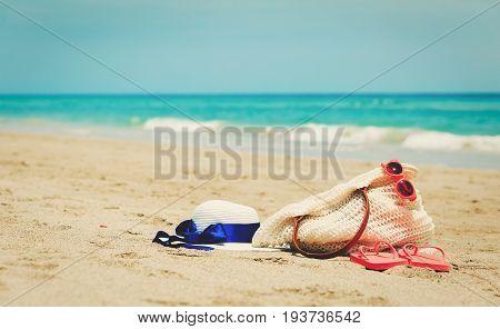 bag, hat suncream, glasses and flip flops on tropical beach