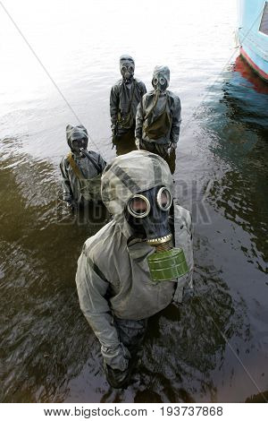 People wearing gas masks and protective suits in civil defense classes