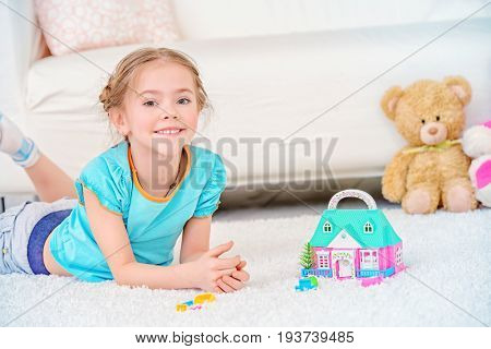 Happy girl child spending time at home, playing with a toy house. Free time, activity and hobby. Family concept.