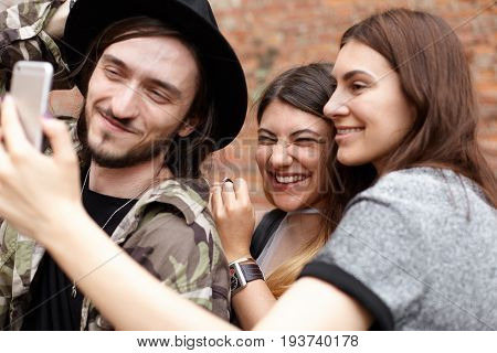 Group of three cheerful best friends laughing having fun outdoors taking selfie on mobile phone sharing pictures via social networks standing against brick wall background. People and technology