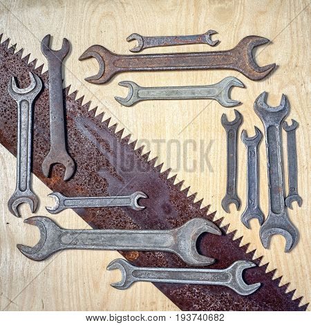 flat lay frame wiith many old rustic wrenches and laying diagonal saw with copy space for your text. suitable as a background for father's day congrats card or ad in the repair shop.
