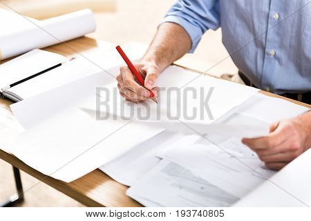 Close up of hands of craftsman sitting at desk and drawing sketches. He is holding in one hand graphite pencil and keeping piece of paper by other hand