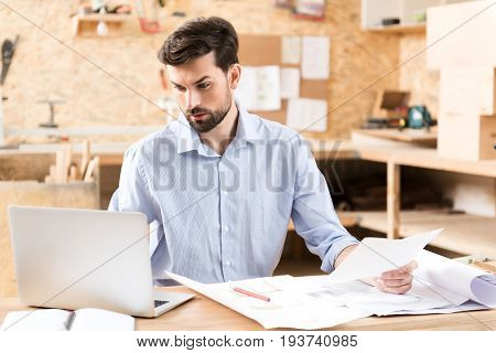 Waist up portrait of serious young woodworker with beard sitting at his desk and doing his job on laptop. He is looking attentively at computer screen and holding paper sheet in other hand