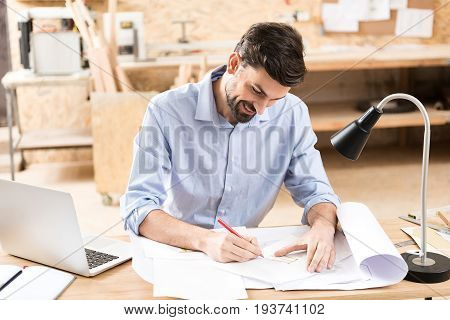 Jolly young wood master is sitting at table in workshop and drawing on piece of paper some sketch by graphite pencil. He is looking down at his draft and smiling