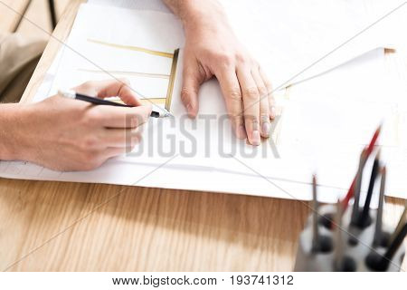Close up of hands of wood master drawing picture of wooden stool on piece of special paper. He is sitting at desk and making draft with help of graphite pencil