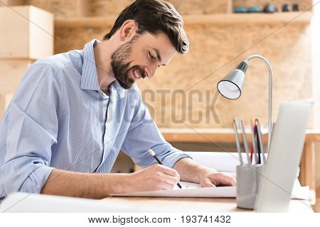 Happy young lumber craftsman with beard is sitting at his desk and drawing some sketch on whatman paper with help of graphite pencil. He is using table-lamp for better illumination