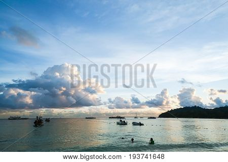 sihouette landscape of sea with boat and people enjoy sunset