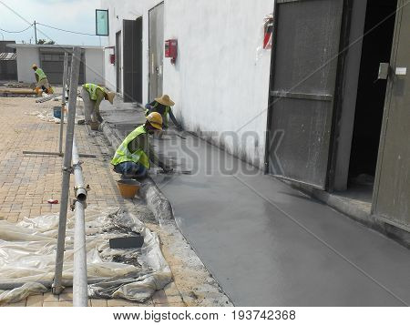 SEREMBAN MALAYSIA -MAY 23 2017: Construction workers leveling wet concrete at the construction site.