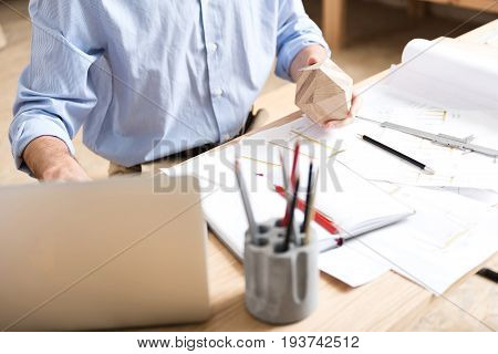 Close up of hands and body of lumber craftsman sitting at desk and holding timber polygon in one hand over paper sketches on table. He is also typing on laptop