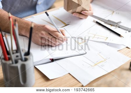 Close up of craftsman sitting at desk and making some calculation of manufacture in his notebook. He is holding timber polygon in one hand while writing by graphite pencil. Sketches lying on desktop
