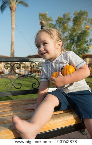 Child Sitting With Two Oranges On Bench