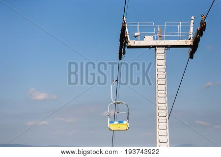 Mountain lift. Ropeway construction against blue clear sky. Yellow cabin moving on cableway, background