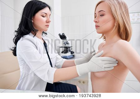 Beautiful young woman getting her breast examined by female doctor gynecologist profession experience trust feminine health medical clinical survey cancer prevention consciousness.