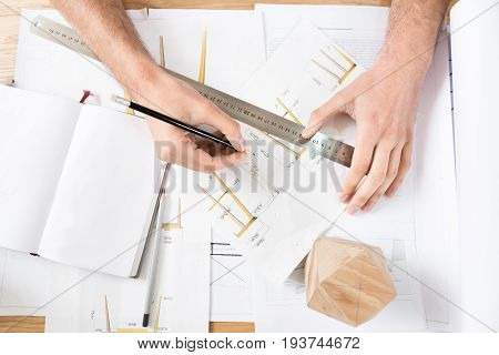 Close up of hands of woodworker making calculations on paper sketches at table. He is using graphite pencil and long ruler. Lumber polygon and open notebook lying on desktop. Top view