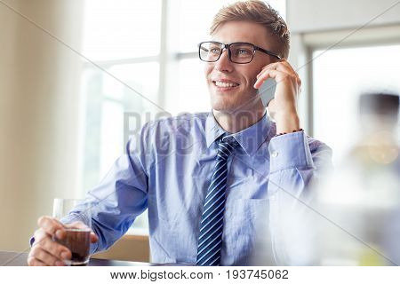 Closeup portrait of smiling adult business man looking away, calling on mobile phone, holding glass of water and sitting at office desk with window in background