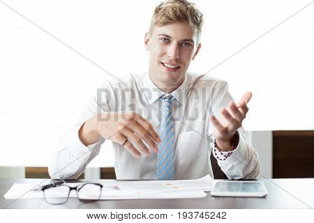 Closeup of smiling adult business man looking at camera, gesturing and sitting at office table. Front view.