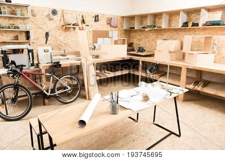 Workshop of lumber craftsman with desk in center full of paper sketches and stationery on it. Various wooden shelves hanging on walls. Tables with instruments and planks built in all around