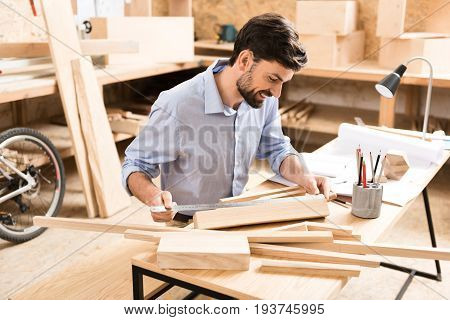 Jolly young lumber craftsman with beard sitting at desk and measuring planks by long aluminium ruler. He is using graphite pencils and whatman paper in his job