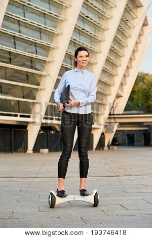 Businesswoman riding hoverboard. Female holding folder. Business administration jobs.