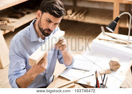Serious young lumber craftsman with beard is sitting at desk and holding horizontally timber strip by both hands close to his face. He is examining surface of plank